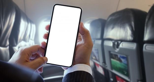 Uomo d'affari che tiene lo smartphone dello schermo in bianco sull'aeroplano
