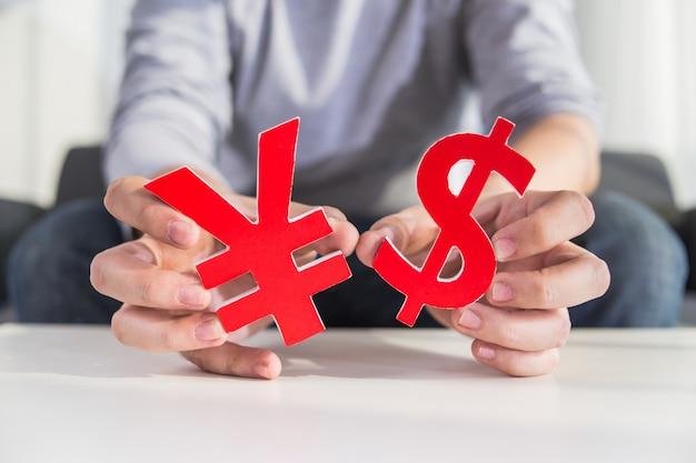 Uomo d'affari che tiene segno del dollaro e cny segno