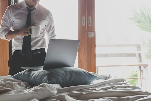 Uomo d'affari che tiene tazza di caffè e che lavora al computer portatile