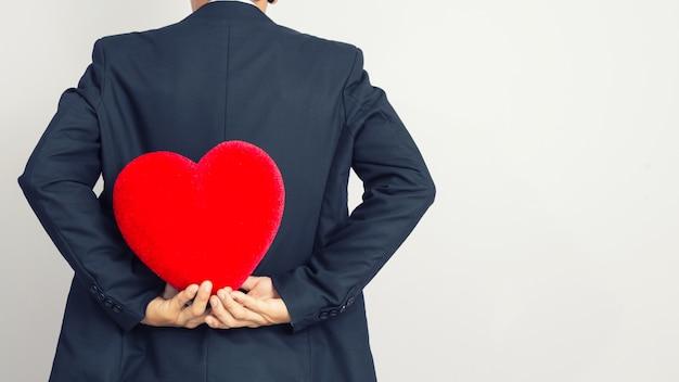 Uomo d'affari che tiene un cuore rosso dietro suo indietro, fondo isolato