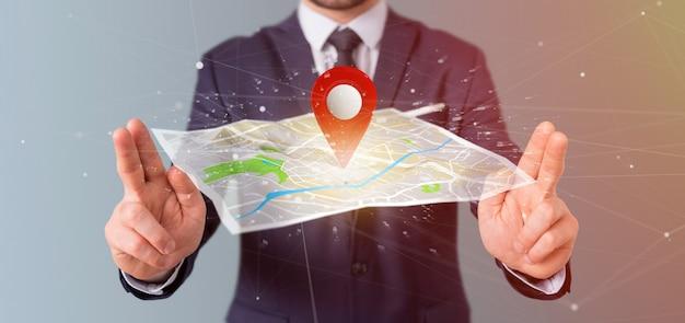 Uomo d'affari che tiene un supporto del perno della rappresentazione 3d su una mappa
