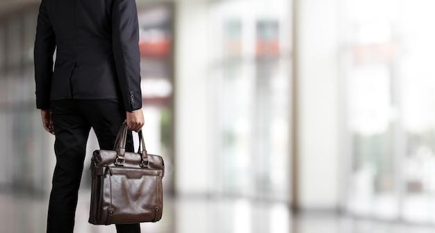 Uomo d'affari che tiene una cartella in un ufficio moderno