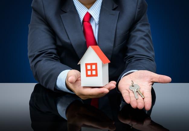 Uomo d'affari che tiene una casa modello e chiave