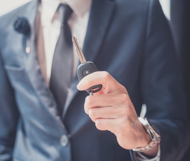 Uomo d'affari che tiene una chiave dell'automobile
