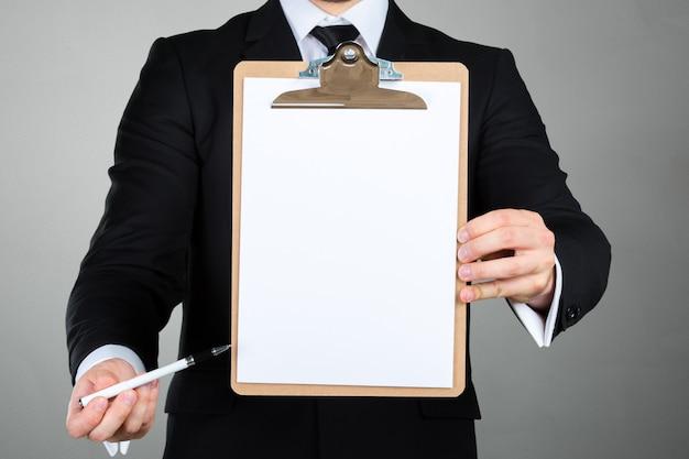 Uomo d'affari che tiene una lavagna per appunti