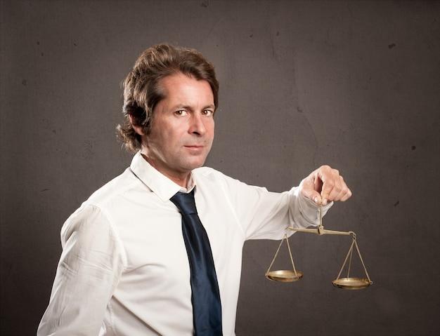 Uomo d'affari che tiene una scala della giustizia