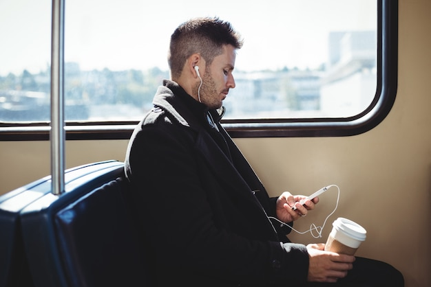 Uomo d'affari che tiene una tazza di caffè eliminabile e che ascolta la musica sul telefono cellulare