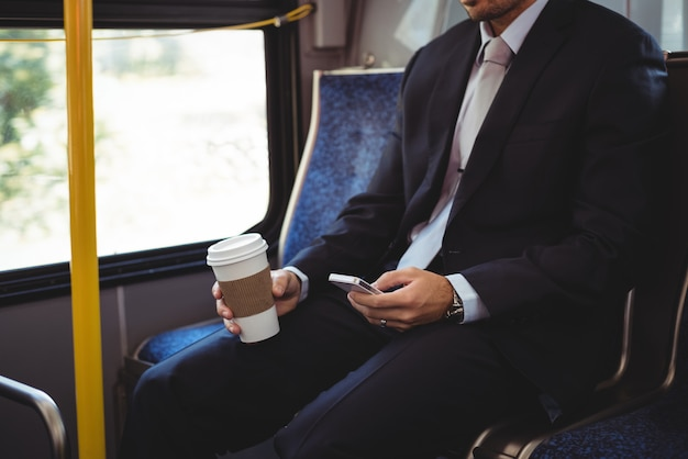 Uomo d'affari che tiene una tazza di caffè eliminabile e che per mezzo del telefono cellulare