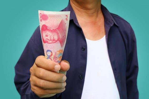 Uomo d'affari che tiene yuan rmb nelle sue mani