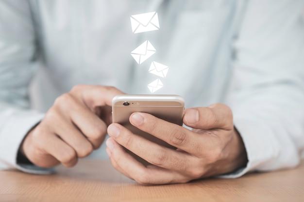 Uomo d'affari che tocca sul monitor del telefono cellulare per inviare posta elettronica (e-mail). lavora da casa o ovunque.