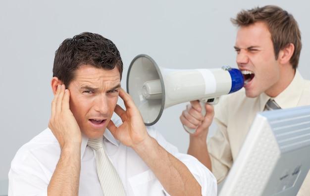 Uomo d'affari che urla tramite un megafono al suo collega