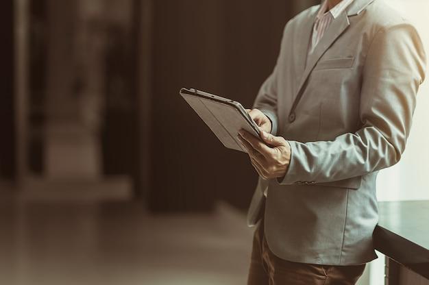 Uomo d'affari che usando tecnologia con la compressa, concetto di internet di tecnologia di affari di servizio di assistenza al cliente di supporto tecnico.