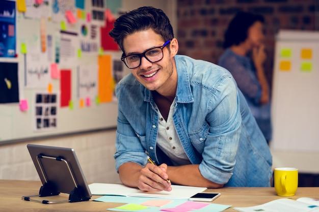 Uomo d'affari che utilizza compressa digitale e che prende le note nel diario