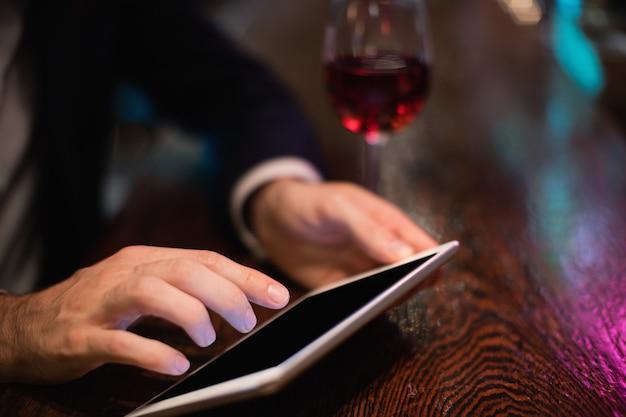 Uomo d'affari che utilizza compressa digitale nel contatore della barra