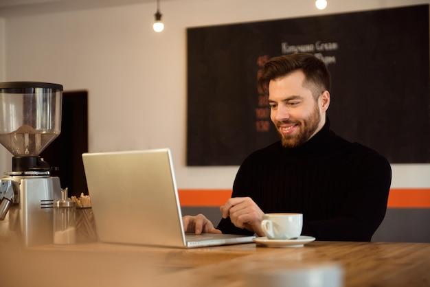 Uomo d'affari che utilizza computer portatile con la compressa sulla tavola di legno nella caffetteria con una tazza di caffè.