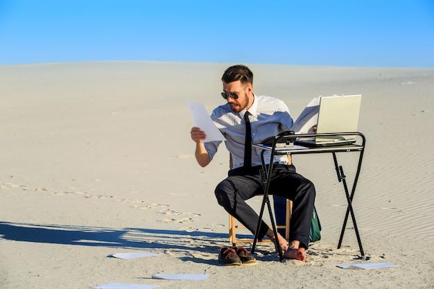 Uomo d'affari che utilizza computer portatile in un deserto