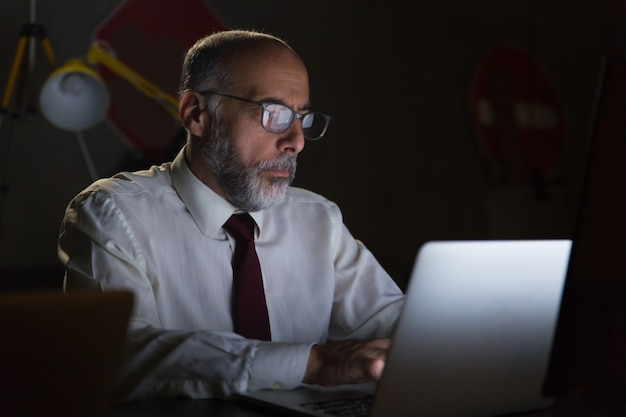 Uomo d'affari che utilizza computer portatile nell'ufficio scuro