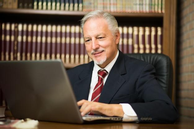 Uomo d'affari che utilizza il suo computer portatile in una biblioteca