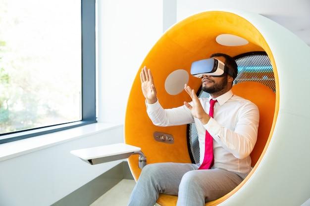 Uomo d'affari che utilizza la cuffia avricolare di realtà virtuale nell'ufficio
