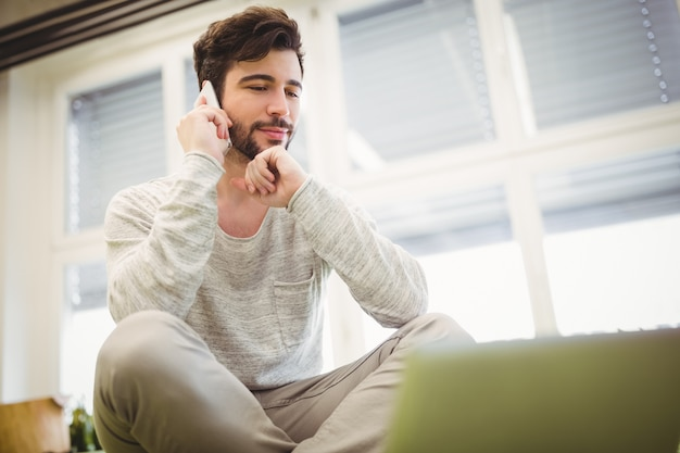 Uomo d'affari che utilizza telefono cellulare nell'ufficio