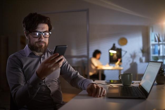 Uomo d'affari che utilizza telefono nel lavoro