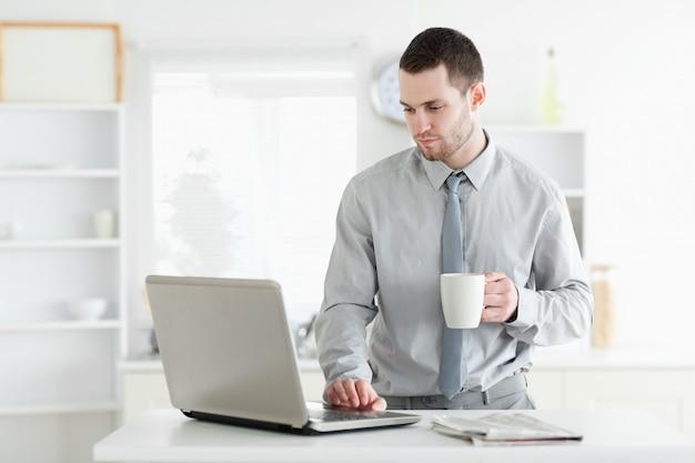 Uomo d'affari che utilizza un computer portatile mentre bevendo caffè
