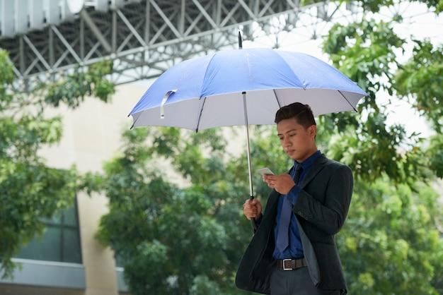 Uomo d'affari cinese che sta con l'ombrello in pioggia e che per mezzo dello smartphone