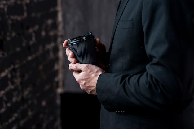 Uomo d'affari con caffè in tazza di carta