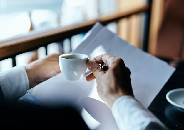 Uomo d'affari con documenti e tazza di caffè pf