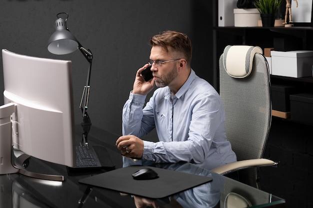 Uomo d'affari con gli occhiali a parlare al telefono in ufficio alla scrivania del computer