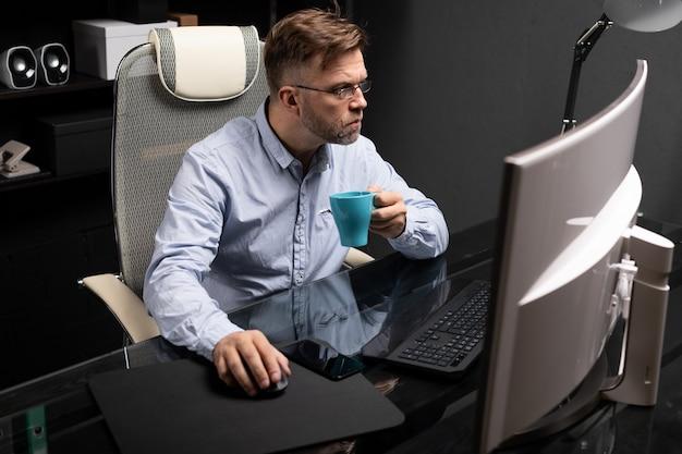 Uomo d'affari con gli occhiali che lavora in ufficio al tavolo del computer e bere caffè da una piccola tazza