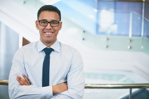 Uomo d'affari con gli occhiali e le braccia conserte
