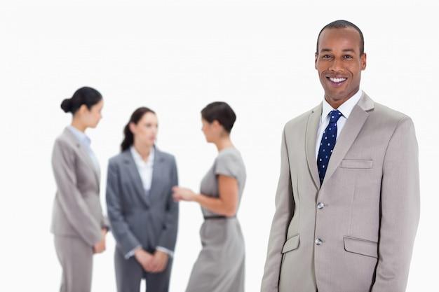 Uomo d'affari con i colleghe che parlano nei precedenti