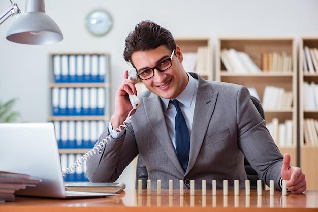 Uomo d'affari con i domino in ufficio