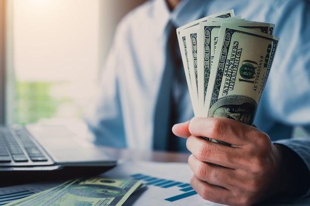 Uomo d'affari con i soldi in mano, dollaro americano, investimenti, successo e concetti di business redditizio.