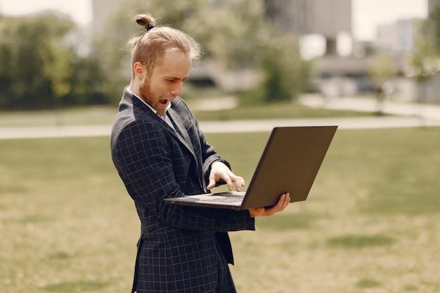 Uomo d'affari con il computer portatile in una città estiva