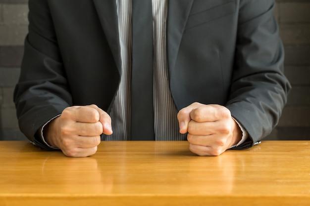 Uomo d'affari con il pugno chiuso sullo scrittorio all'ufficio
