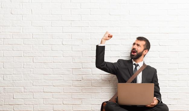Uomo d'affari con il suo computer portatile che si siede sul pavimento che celebra una vittoria nella posizione del vincitore