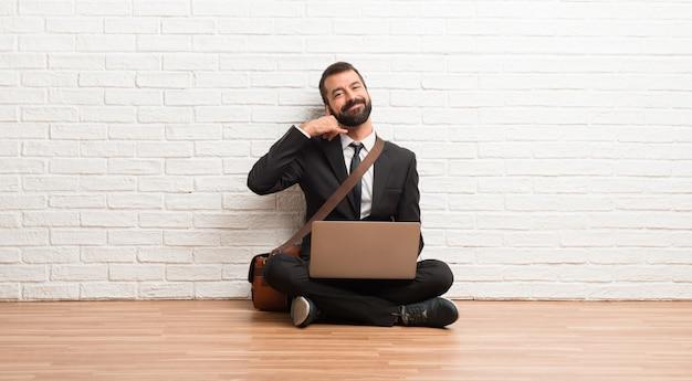 Uomo d'affari con il suo computer portatile che si siede sul pavimento che fa gesto del telefono. chiamami segno