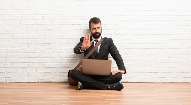 Uomo d'affari con il suo computer portatile che si siede sul pavimento che fa il gesto di arresto che nega una situazione che pensa sbagliato