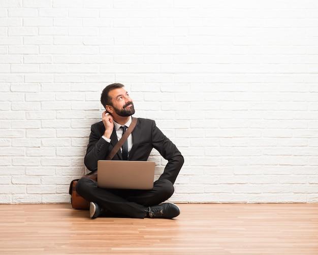 Uomo d'affari con il suo computer portatile che si siede sul pavimento che sta e che pensa un'idea mentre graffiando si dirige