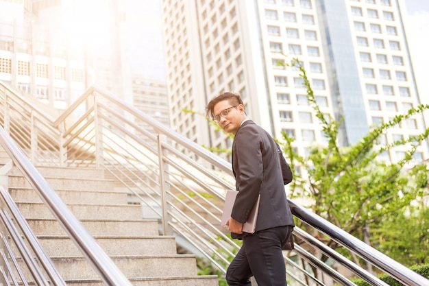 Uomo d'affari con il suo portatile salendo le scale in un'ora di punta a lavorare