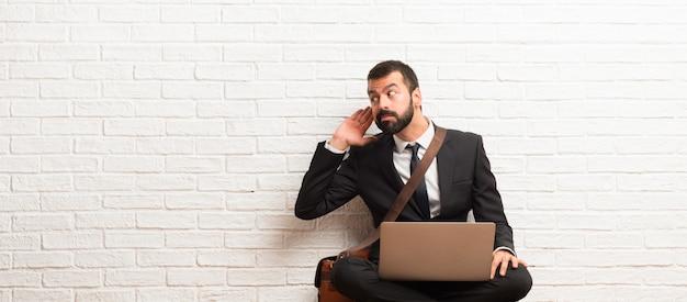 Uomo d'affari con il suo portatile seduto sul pavimento ascoltando qualcosa mettendo la mano sull'orecchio