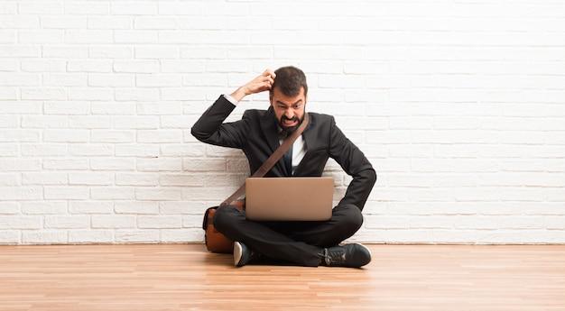 Uomo d'affari con il suo portatile seduto sul pavimento avendo dubbi mentre grattando la testa