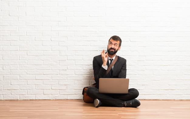Uomo d'affari con il suo portatile seduto sul pavimento con le dita che attraversano e che desiderano il meglio