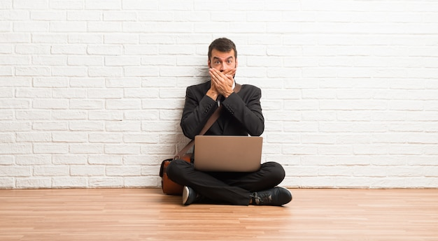 Uomo d'affari con il suo portatile seduto sulla bocca del pavimento con entrambe le mani