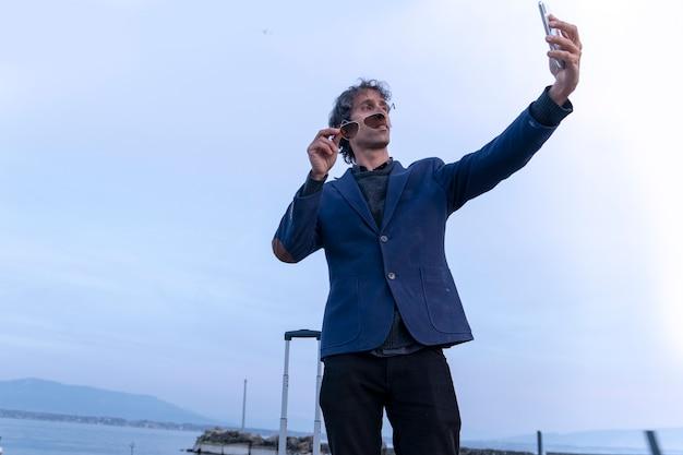 Uomo d'affari con il telefono cellulare che fa un autoritratto sul molo in svizzera
