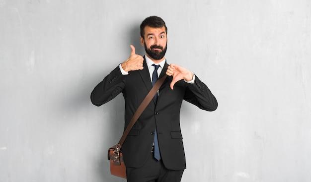 Uomo d'affari con la barba che fa segno di buono-cattivo. indeciso tra sì o no