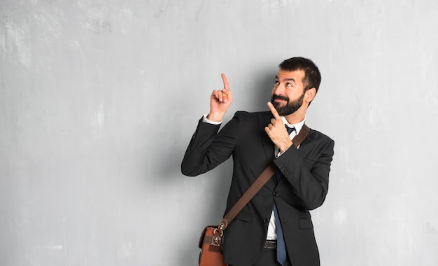 Uomo d'affari con la barba che indica con il dito indice e alzando lo sguardo