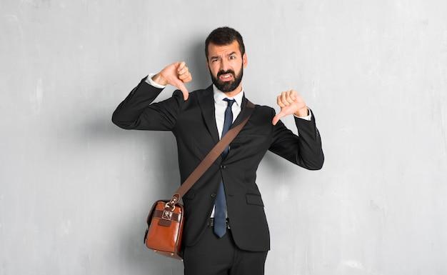 Uomo d'affari con la barba che mostra pollice giù con entrambe le mani